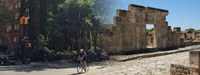 Composite photo showing cyclists at tree-lined New York City intersection and the archaeological remains of an ancient building in Tunisia.