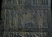 Inscribed black stone surface with cuneiform texts and a group of seven people engaged in ritual performance.