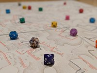 Photo of game dice of various colors on a topographical site plan.