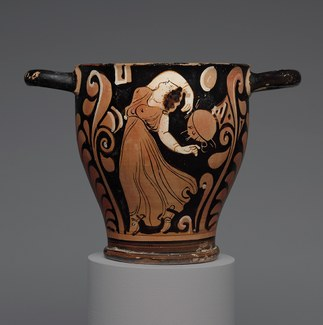 photo of a terracotta skyphos with a dancing maenad decoration
