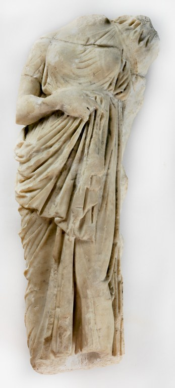 Statuette of a woman's body in a heavily draped dress, missing head, feet, and one arm.