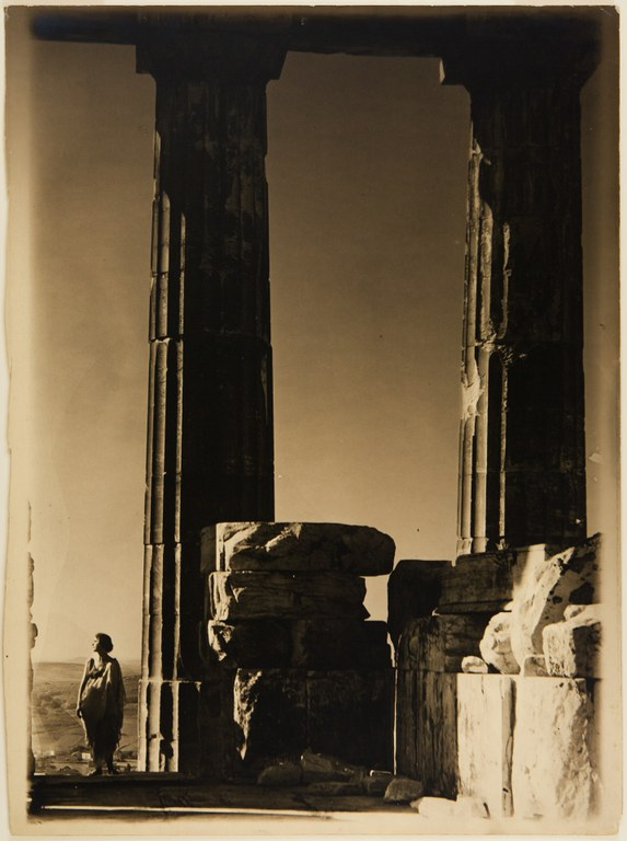 Photograph depicting two large, fluted columns and a woman wearing an ancient-style dress standing beside them. She faces the camera with her head turned to her right to face the sun.