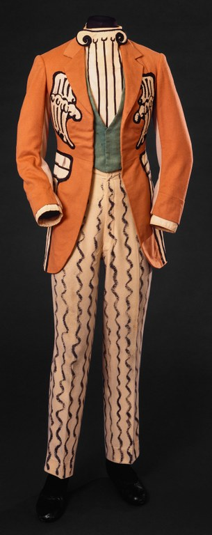 Three-piece suit. Colors on the garment are orange, pale orange, green, and black. Patterns include architectural elements such as a painted column dickey, stone-style applique, and squiggly lines on the trousers.