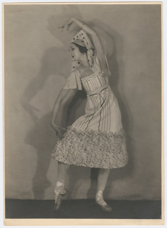 Photograph of a ballerina striking a pose with her hand above her head, wearing a dress with a column painted on it.