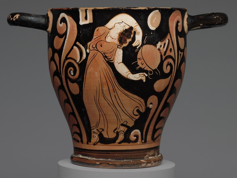 Tapered vessel with two handles, glazed in red, black, and white, depicting a dancing woman in a long sleeveless dress.