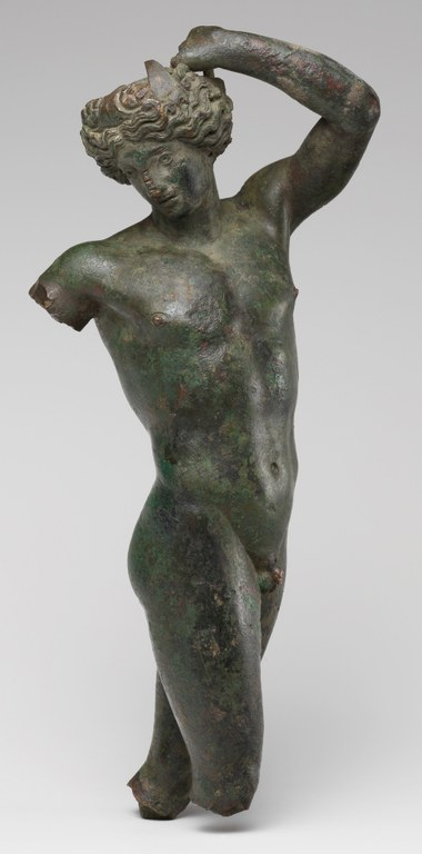 Statuette of a dancing young man. The figure is missing his legs below the knees, and one arm.