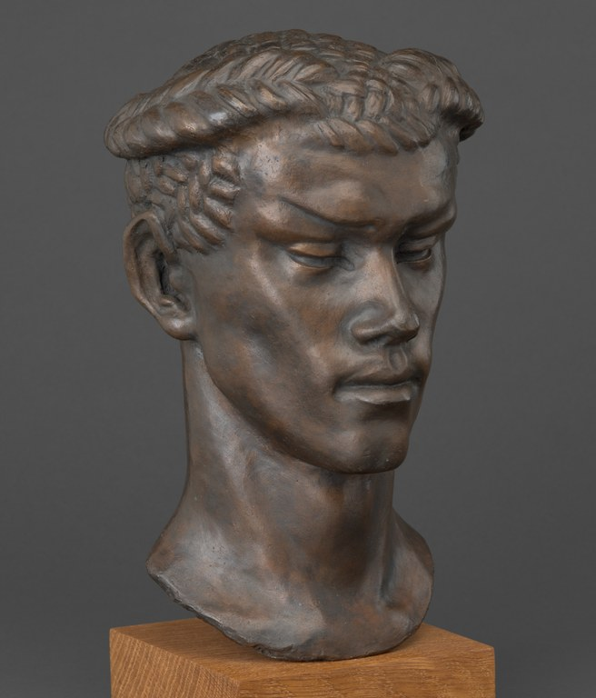 Bust of an unsmiling man with elongated face, prominent brows, and a laurel crown on his head. The figure is recognizable as Vaslav Nijinsky in character as the Faun.
