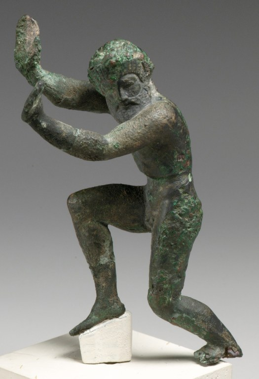 Statuette of a bearded male figure dancing with one leg raised and arms elevated.
