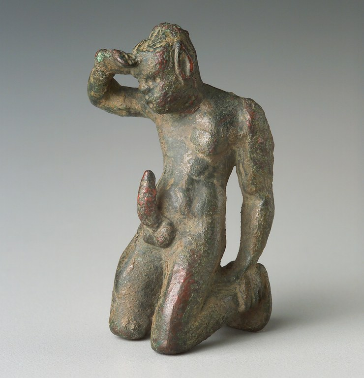 Statuette of a bearded male figure with prominently pointed ears, kneeling in an exaggerated ithyphallic pose with one hand at eyebrow level.