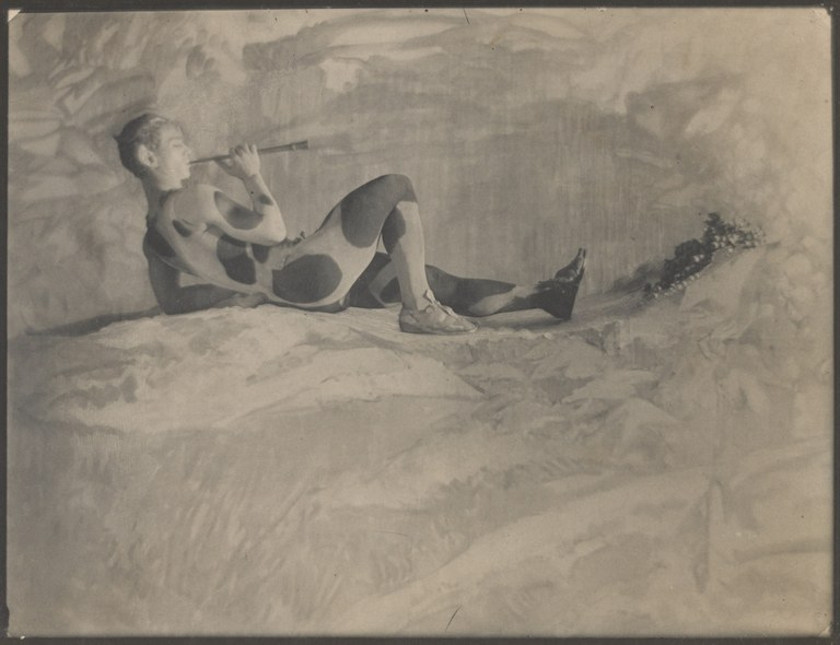 Photograph in a painterly style depicting a man wearing an animal print leotard, lying down on a rock and playing a musical pipe.