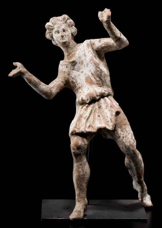 Statuette of a dancing, curly-haired youth with arms raised. He wears a short, sleeveless tunic that is belted or tied at the waist and that leaves his knees bare.