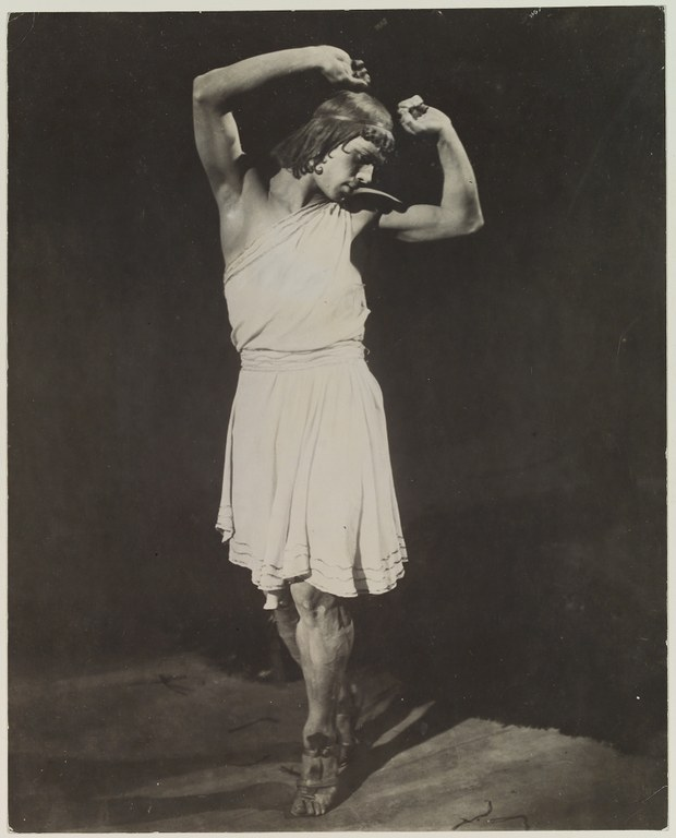 Photograph of a man dancing with hands raised above his head. He wears a short, sleeveless tunic that is tied at the waist and that leaves his knees bare.