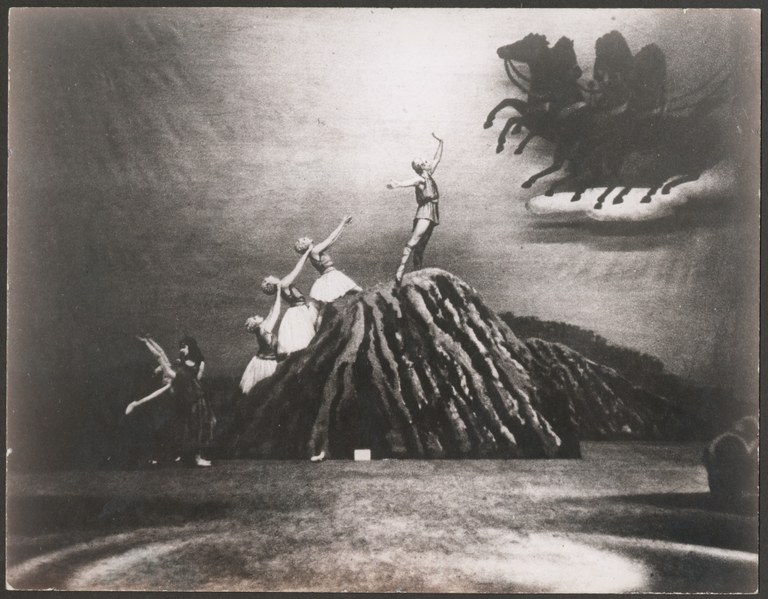 Photograph of multiple dancers on a stage. A male dancer wearing a short, sleeveless tunic stands at the top of a mountain, reaching his arm up toward a chariot on a cloud that is pulled by four horses. Below and behind him are three female dancers with sleeveless short dresses, gesturing toward him. On the stage floor below, are two more women wearing long tutus with sleeveless bodices.