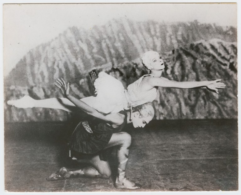 Photograph of a male dancer wearing a short, sleeveless tunic. He crouches on one knee, supporting a ballerina wearing a short sleeveless dress in a horizontal pose on his back.