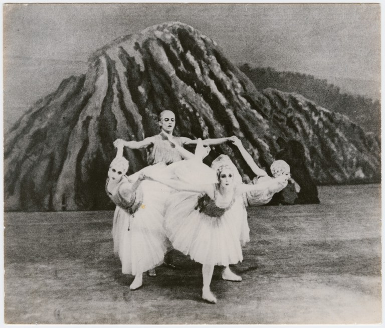Photograph of three ballerinas in an arabesque pose before a male dancer with his arms extended.