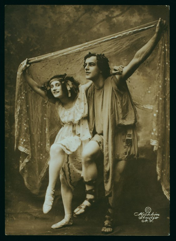 Photograph of male and female dancers bent slightly at waist, each with a knee raised, holding fabric above their heads. The woman wears a sleeveless dress that extends to mid-calf. The man wears a sleeveless tunic, belted at the waist, that extends to mid-thigh.