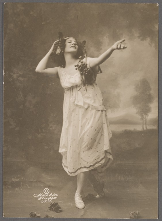 Photograph of a woman in a long dress with one arm bent and touching her head, and the other arm extended as she steps toward the camera.  She wears a sleeveless dress that extends to mid-calf and bunches of grapes are draped around her head and over her shoulders.
