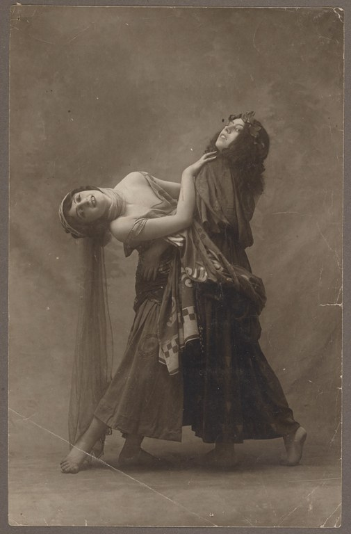 Photograph of two female dancers in long, sleeveless dresses. The two women are in an embrace: one bends backward, pulling away from the other.