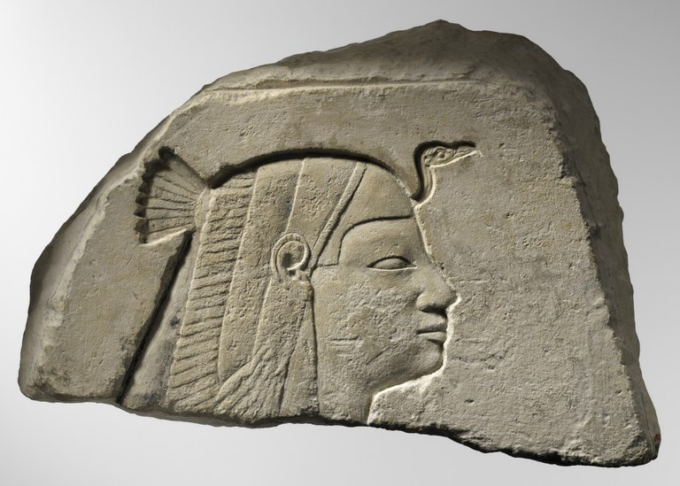 Egyptian stone relief of a female head, in profile, with a vulture headdress.