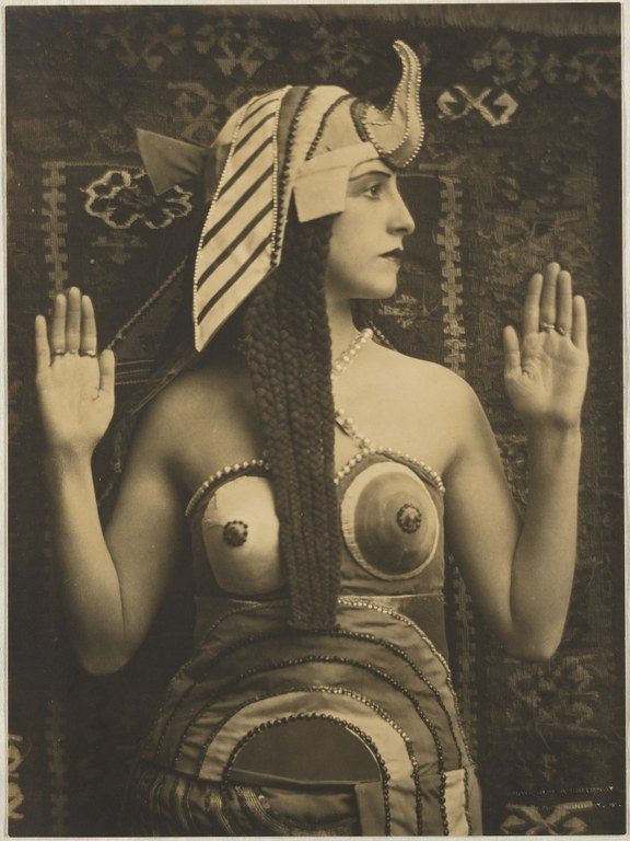 Photograph of a woman dressed in a costume inspired by ancient Egyptian clothing. She faces the camera with her head turned right and hands raised at the elbows. Her dress is patterned in bold geometric shapes and she wears an elaborate vulture headdress on her head