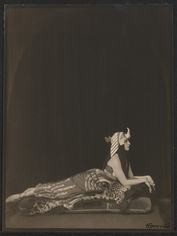 Photograph of a woman dressed in a costume inspired by ancient Egyptian clothing. She lies on her front facing right, raising her torso on her elbows.