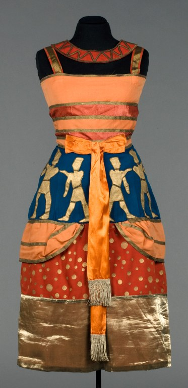 A colorful woman's knee-length dress, with straps and a collar, belted at waist with a bow. Horizontal stripes and patterns in orange, red, blue, and gold.