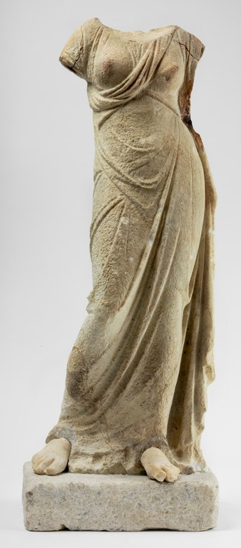 Statuette of a female in contrapposto pose wearing a long gown, missing head and arms.