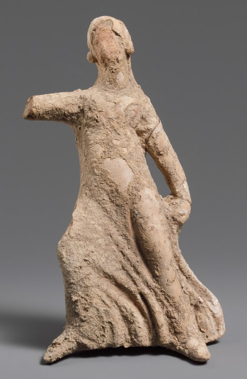 Statuette of a faceless girl dancing, wearing a long dress and missing one arm at the elbow.