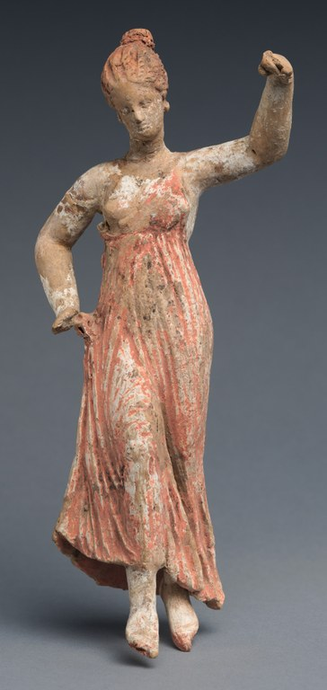 Statuette of a woman dancing on her toes with one arm raised, wearing a long sleeveless dress. Both hands are missing.