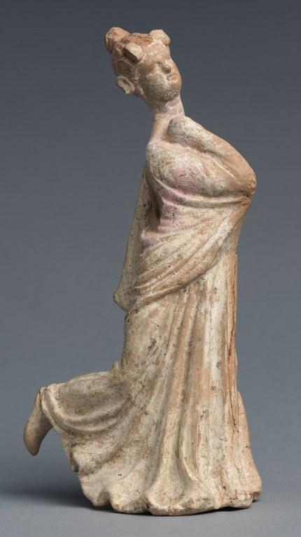 Statuette of a woman dancing wearing a long dress.