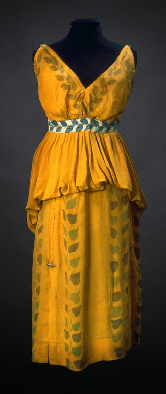 A yellow, sleeveless dress for a woman with painted green ivy leaves in a vertical pattern.