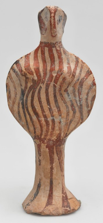 """Ceramic figurine in the stylized shape of the Greek letter """"Phi"""" with brown vertical stripes from the midpoint of the figure up."""