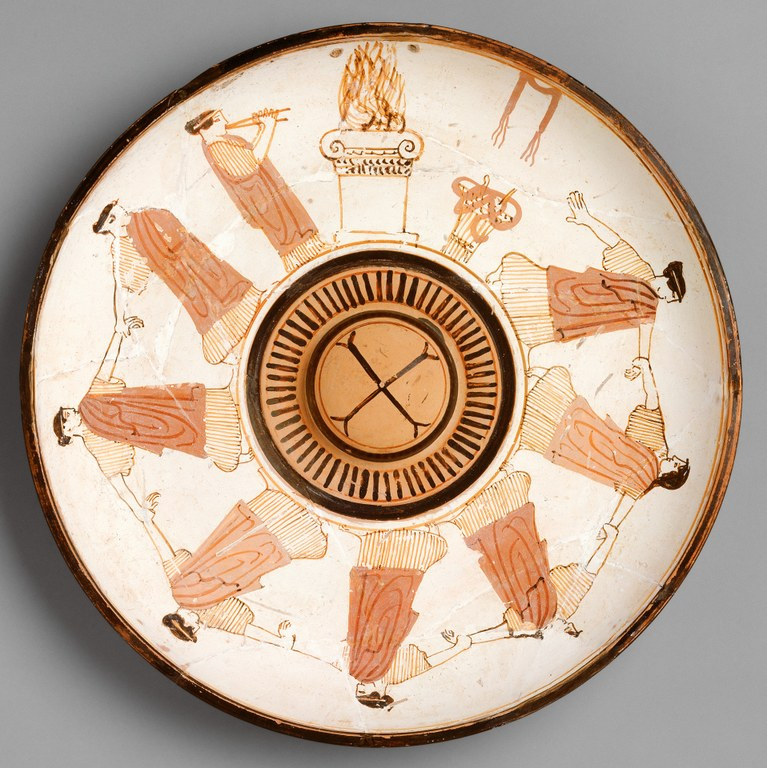 White terracotta plate with decoration in reddish-orange and black. Eight young women dressed in long robes are shown dancing with interlocking hands. One plays a double flute. A fire burns on an altar and other decorative or ritual objects are depicted.