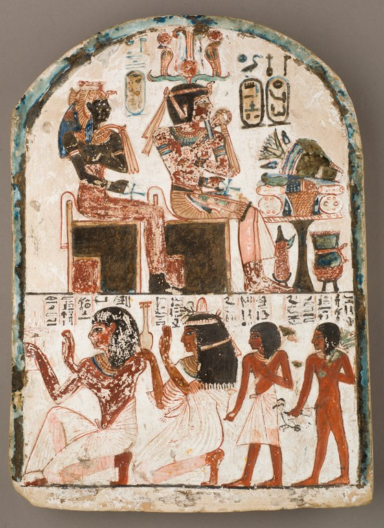 A painted stele with a rounded top. It is decorated in two registers on a white ground. The top register features two seated figures in profile and a table laden with objects. Cartouches and other signs appear above the figures. Four figures appear in the bottom register, also in profile, but facing the opposite direction. The first two figures kneel and raise their hands, while the second two stand behind them and appear to be much smaller. Several rows of hieroglyphic writing appear above these four figures.