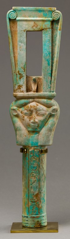 Rattle-like instrument in turquoise color with Egyptian hieroglyphs on the handle, which is topped by a stylized head. Above the head, the empty rectangular frame would have originally held the noise-making portion of the instrument.