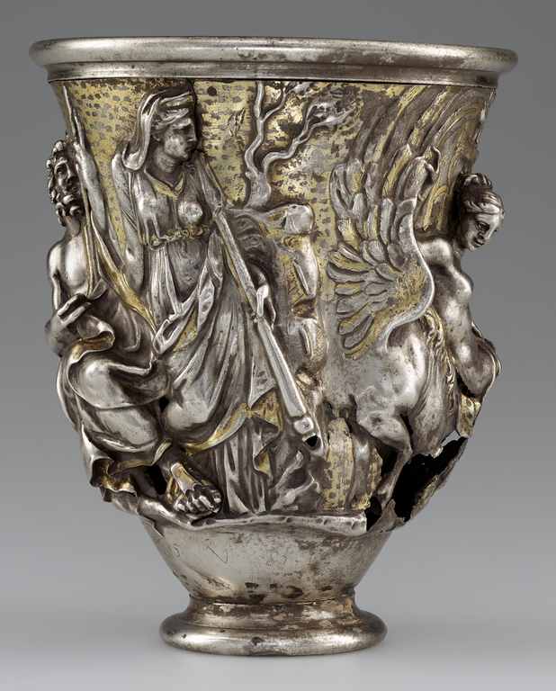 Photograph of a silver and gold beaker, richly decorated with figures in raised relief.