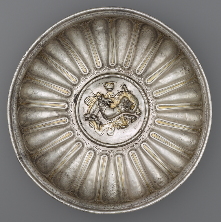 Picture of a shallow, decorative bowl made of silver and gold. In the center is a medallion depicting a woman sleeping on a lion skin, surrounded by a club and other objects.