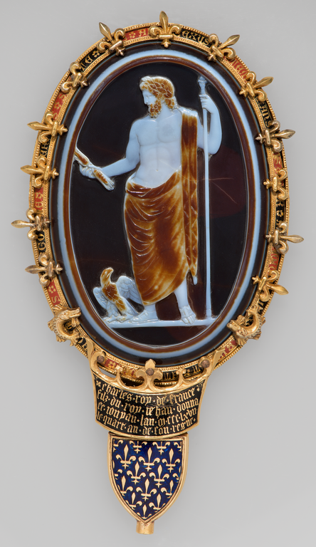 Photograph of oval cameo depicting a standing, bearded male figure with an eagle at his feet. The figure holds a long staff vertically in one hand and a thunderbolt, at which he gazes, in the other. The cameo is set in an elaborate frame of gold and enamel.