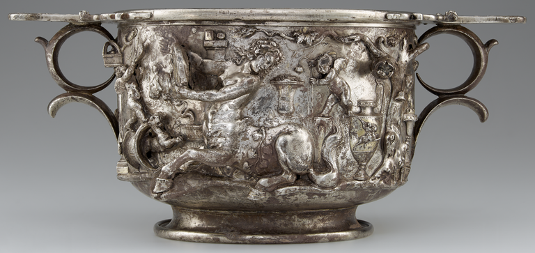 Photograph of a silver and gold two-handled cup, richly decorated with figures in raised relief.