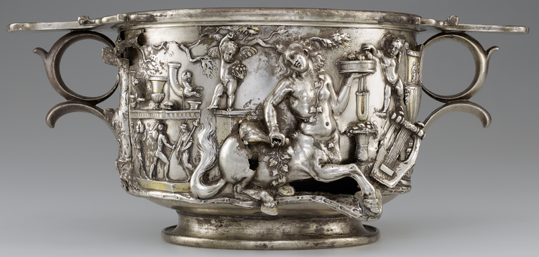 Photograph of a silver and gold two-handled cup, richly decorated with figures in raised relief