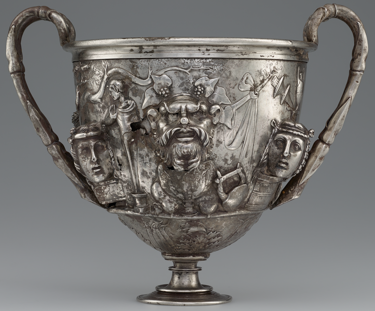 Photograph of a silver two-handled cup, richly decorated with figures in raised relief.