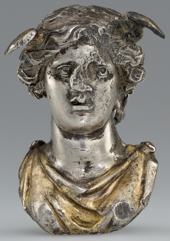 Photograph of silver and gold bust of a female figure with small wings on her head.