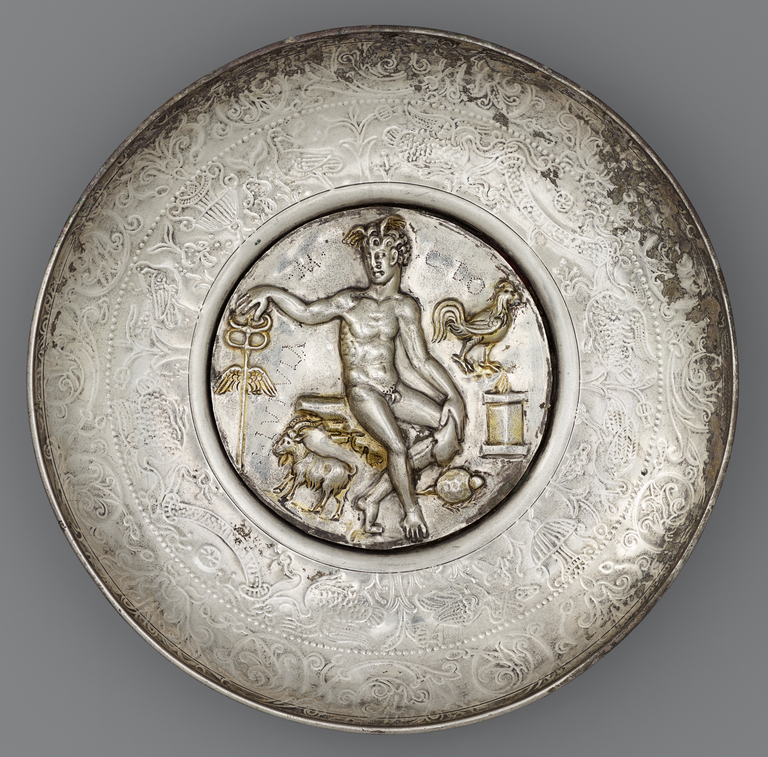 Photograph of a silver bowl with a large central medallion depicting a nude, seated Mercury with caduceus and wings on his head. An altar, a rooster, a ram, and a tortoise are also depicted.