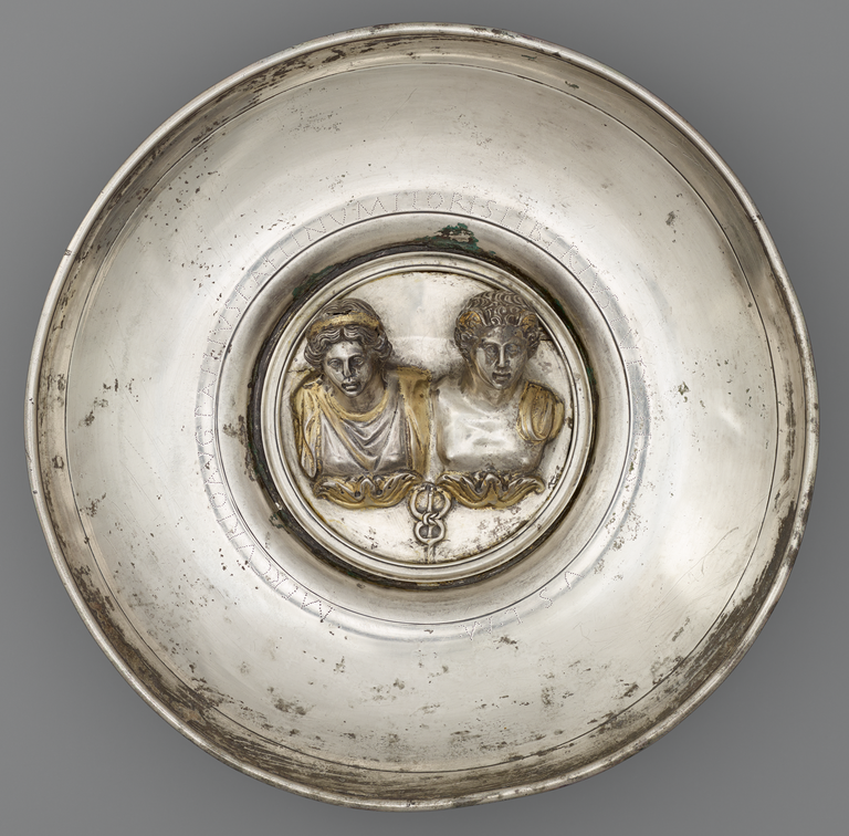 Photograph of a silver offering bowl with a large, central medallion in silver and gold depicting two busts: one male and one female. A caduceus appears below the busts.