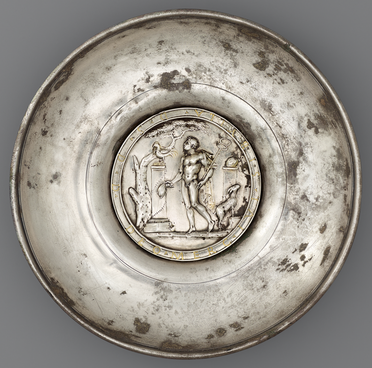 Photograph of a silver offering bowl with a large, central medallion depicting Mercury, nude with caduceus, standing before a tall pedastal or altar. A tree, a chicken, and a goat are also shown.