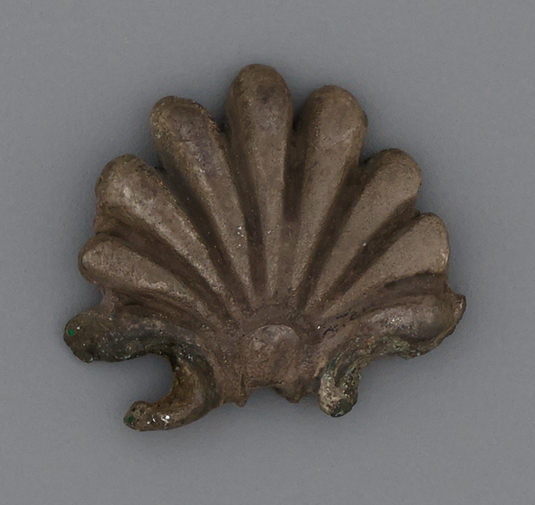Photograph of a corroded silver palmette.