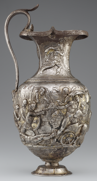 Photograph of a silver and gold pitcher richly decorated with figures in raised relief.
