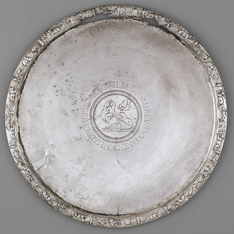 Photograph of a silver plate with a central medallion bearing a hunting scene, surrounded by an incised Latin text. The plate's rim is decorated with animals, buildings, and other objects.