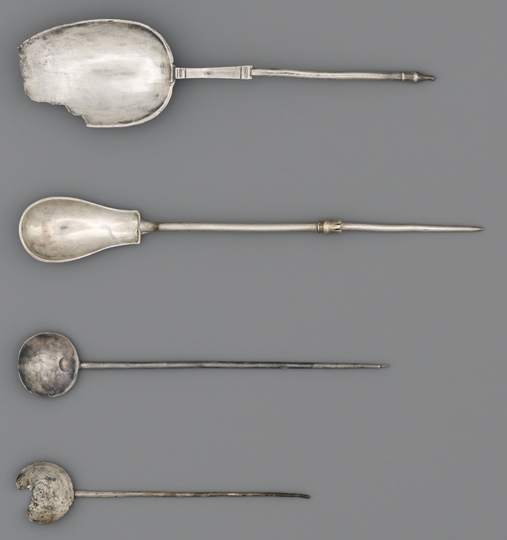 Photograph of four silver spoons, two with circular bowls, the other two larger and elongated in form.