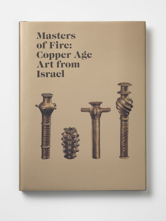 Photograph of the front cover of the volume. It is a light brown color, with the title at upper left in black ink. Images of four of the objects from the exhibition fill the remaining space.